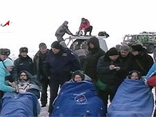 Expedition 34 rests at the Kazakhstan<br /> landing site with the recovery crew<br /> and Soyuz TMA-06M behind them.<br /> Credit: NASA TV